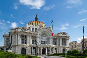 a large stone statue in front of Palacio de Bellas Artes