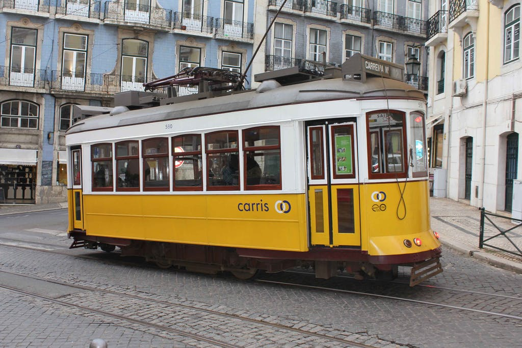 a yellow train traveling down a city street