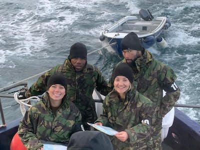 a group of people in uniform sitting on a boat
