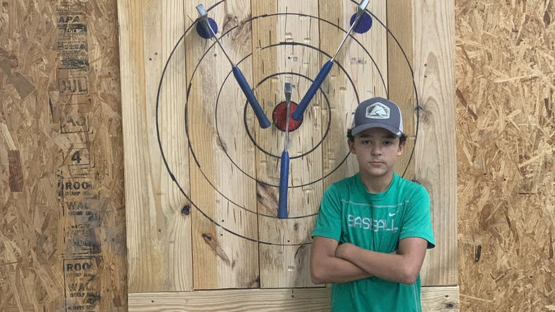 kid standing next to axe throwing target