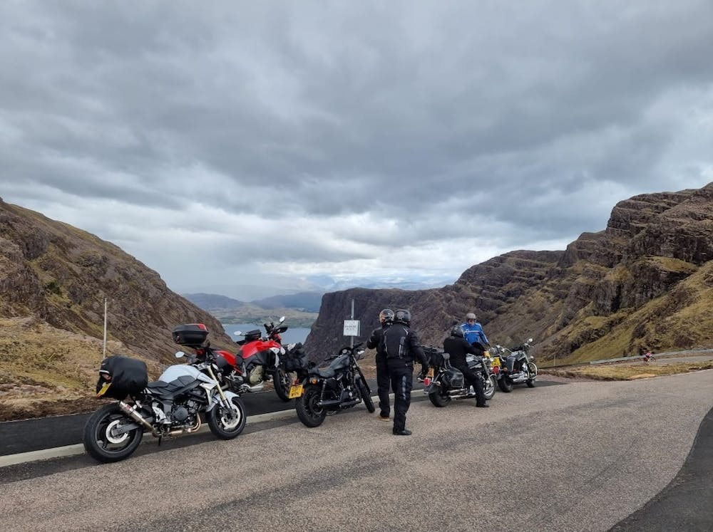 a motorcycle is parked on the side of a mountain road