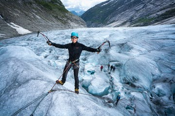 man ice climbing on glacier