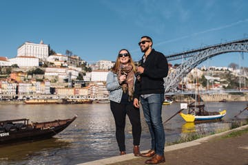 Guests enjoying food and wine tour in Porto next to bridge | Uncorked Vines