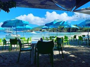 a lawn chair under an umbrella on a beach