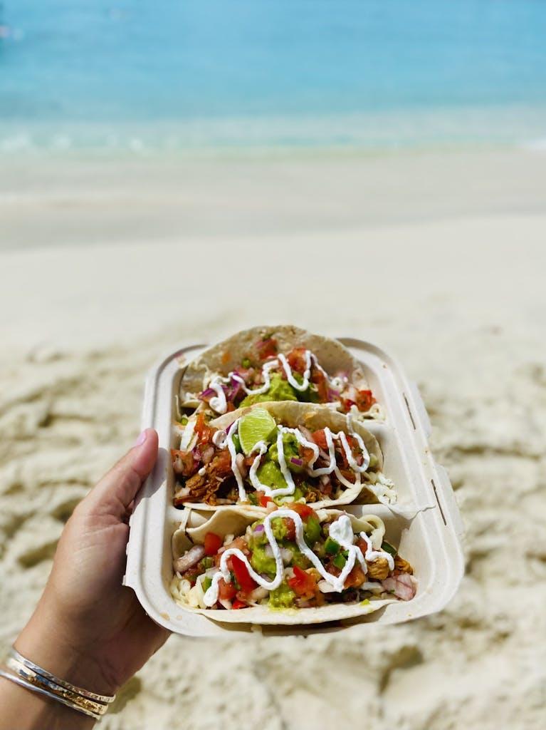 a hand holding tacos on a beach
