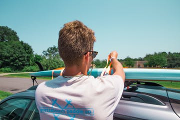 man wrapping the board on top of the car