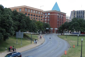 a car parked on the side of a road with Dealey Plaza in the background