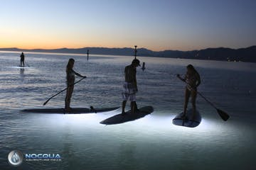 people standup paddleboarding at night