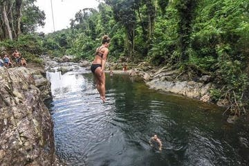 woman jumping to a river