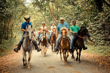 a group of people riding horses on a dirt road