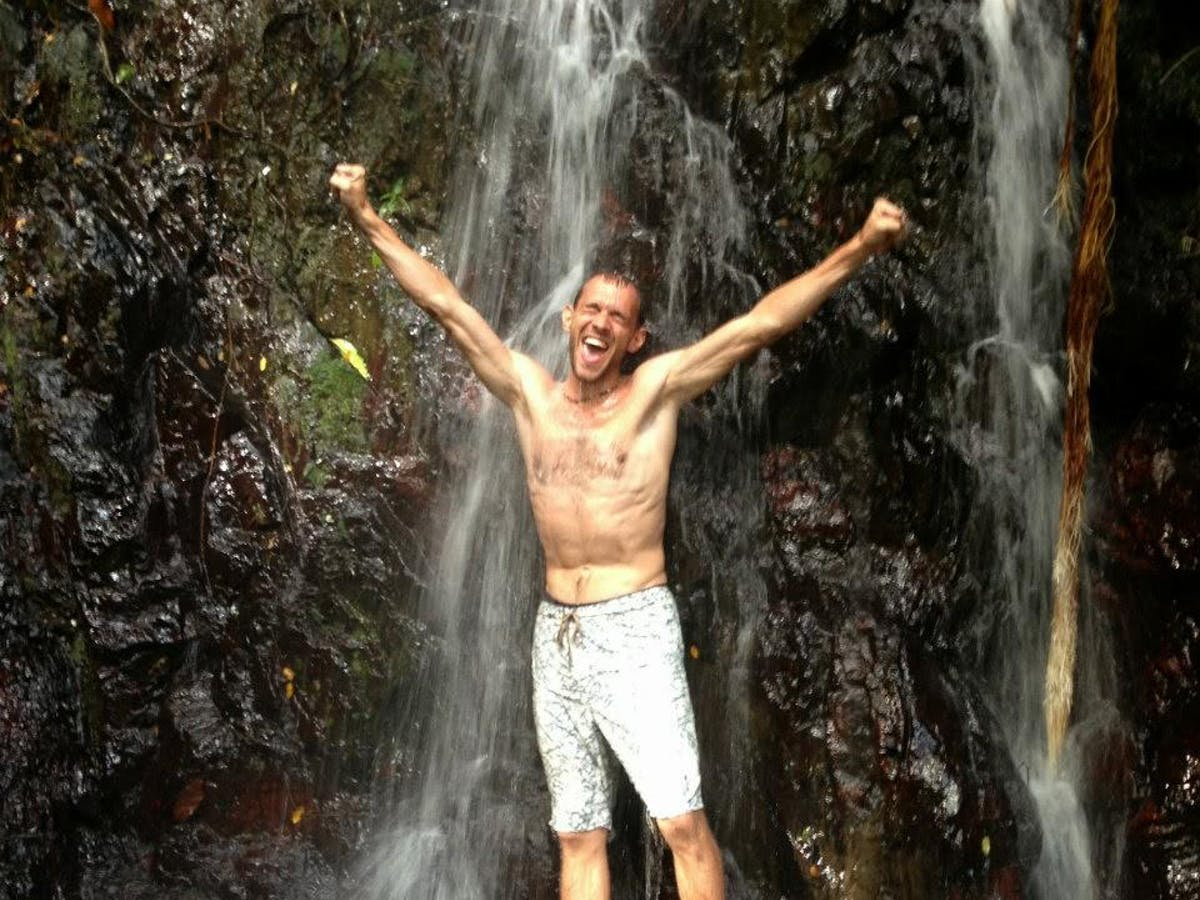 a man standing next to a waterfall