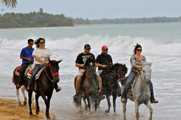 a group of people riding horses on a beach near a body of water
