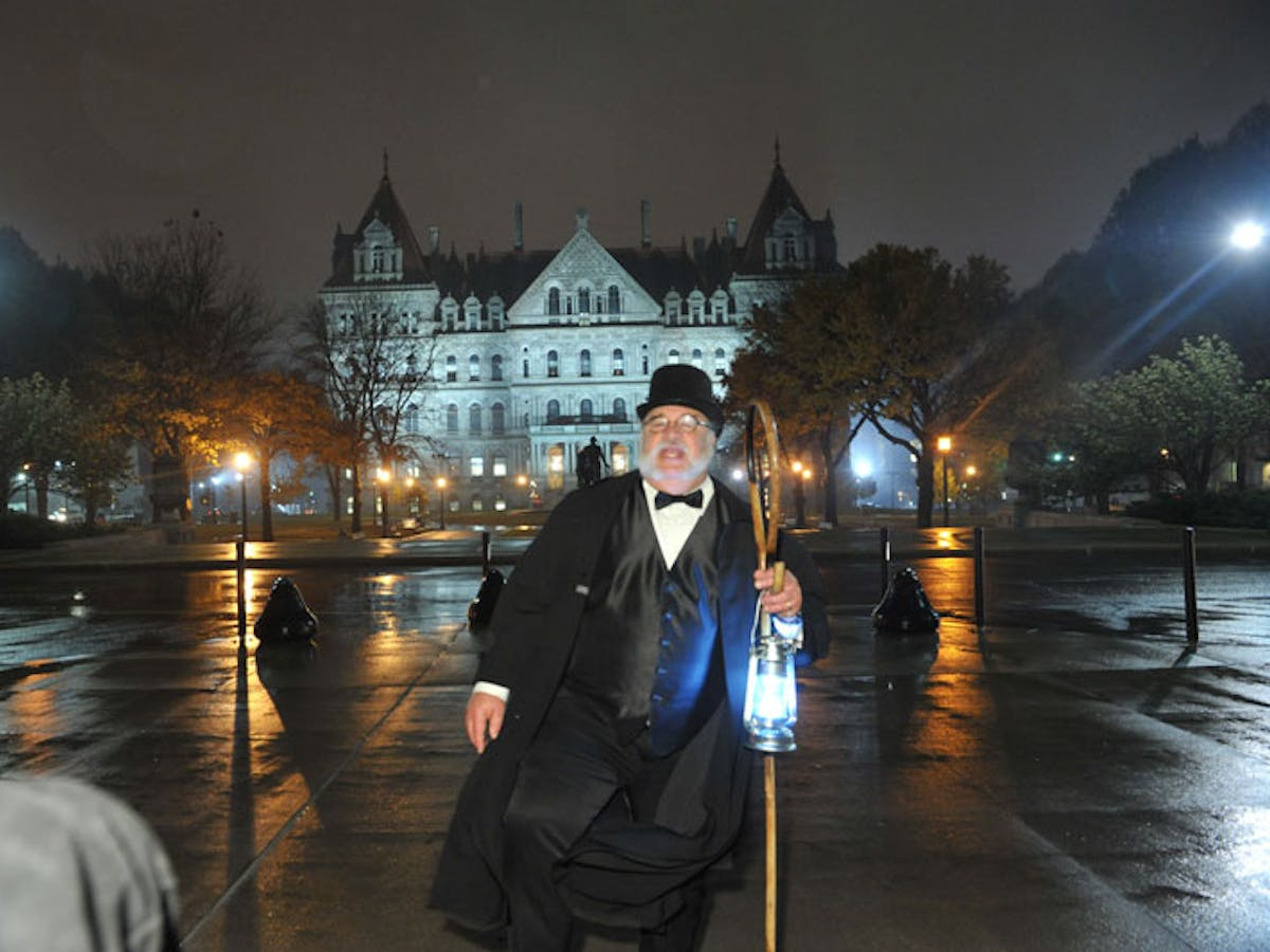 a man in a wet suit standing on a rainy night