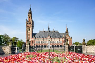 a group of people in front of a large church with Peace Palace in the background