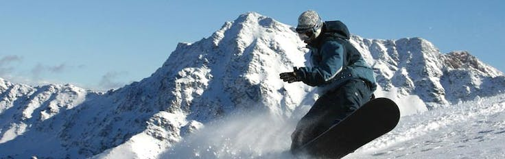 a man riding a snowboard down a snow covered mountain