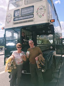 a man and a woman standing in front of a bus