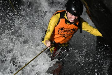 a man wearing a wet suit riding a surf board in the snow