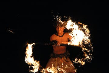 a person in a dark room with smoke and fire