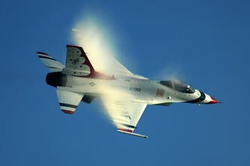 a fighter jet flying through a blue sky