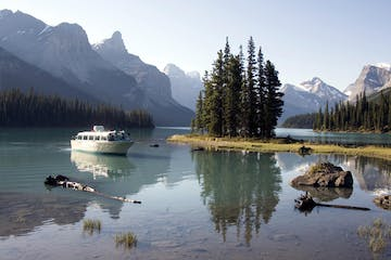 a small boat in a body of water with Maligne Lake in the background