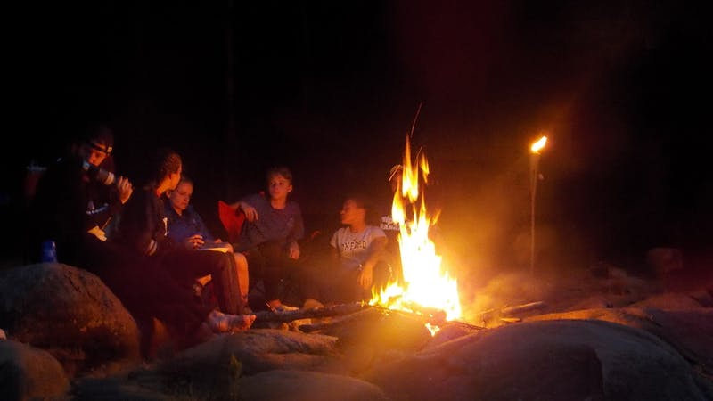 a group of people sitting around a fire
