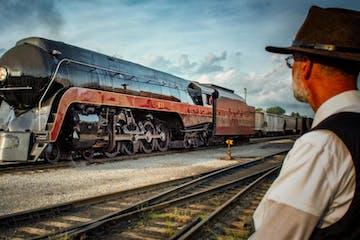 a man standing next to a train