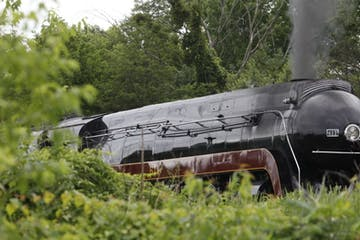 a steam engine train traveling down train tracks near a forest