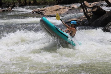 a person riding a wave on an inflatable kayak in the water, on the river