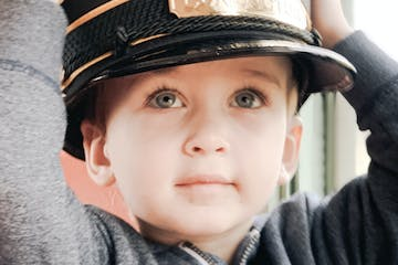a close up of a boy wearing a hat