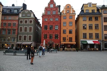 a group of people walking in front of Gamla stan