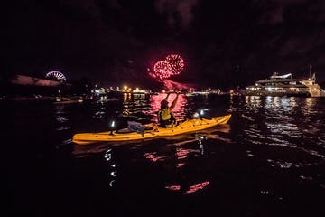 a man in a boat with fireworks