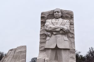 a large stone statue of a person with Martin Luther King Jr. Memorial in the background
