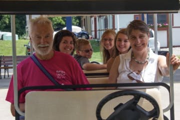 a group of people sitting on a golf cart