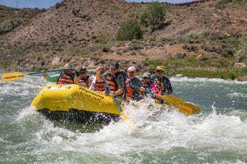 a group of people riding on a raft in a body of water