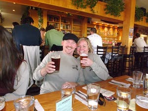 man and women smiling with beers in hand