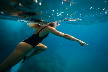 a woman swimming in a pool of water