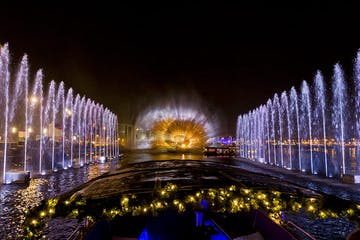 a fountain in front of a large bridge lit up at night