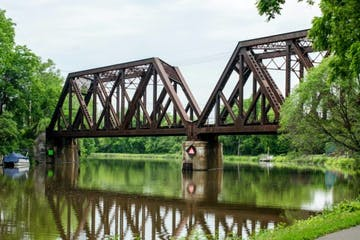a train crossing a bridge over a body of water