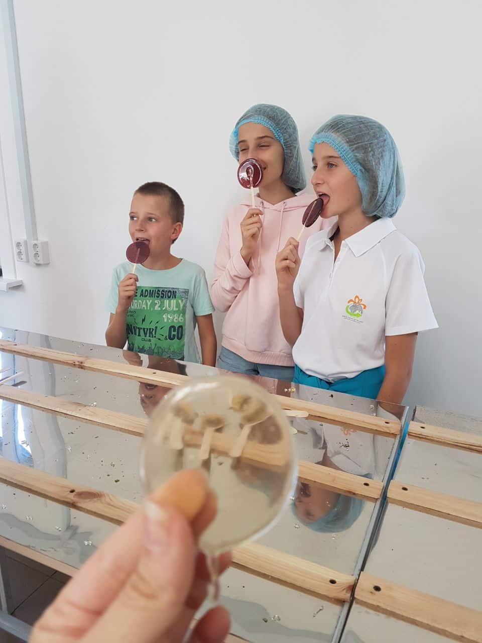 Children licking lollypops in Russian honey farm village
