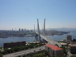 a bridge over a body of water with a city in the background