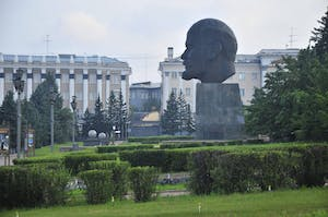 a large building with a statue in a park