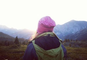 a person wearing a purple hat with a mountain in the background