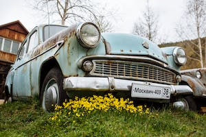an old car parked in a grassy field