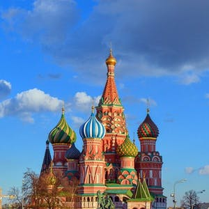 a church with a clock tower with Saint Basil's Cathedral in the background