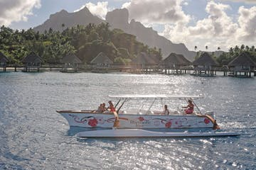 An outrigger canoe sailing in Bora Bora at sunset time