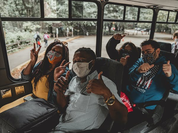 group of people on bus wearing masks
