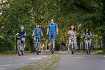 a group of people riding on the back of a bicycle
