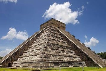 a large brick building with Chichen Itza in the background