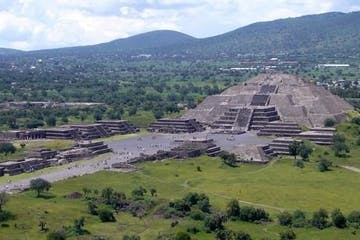 a large green field with Teotihuacan in the background