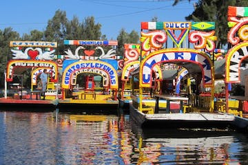 a boat that is floating in the water with Xochimilco in the background